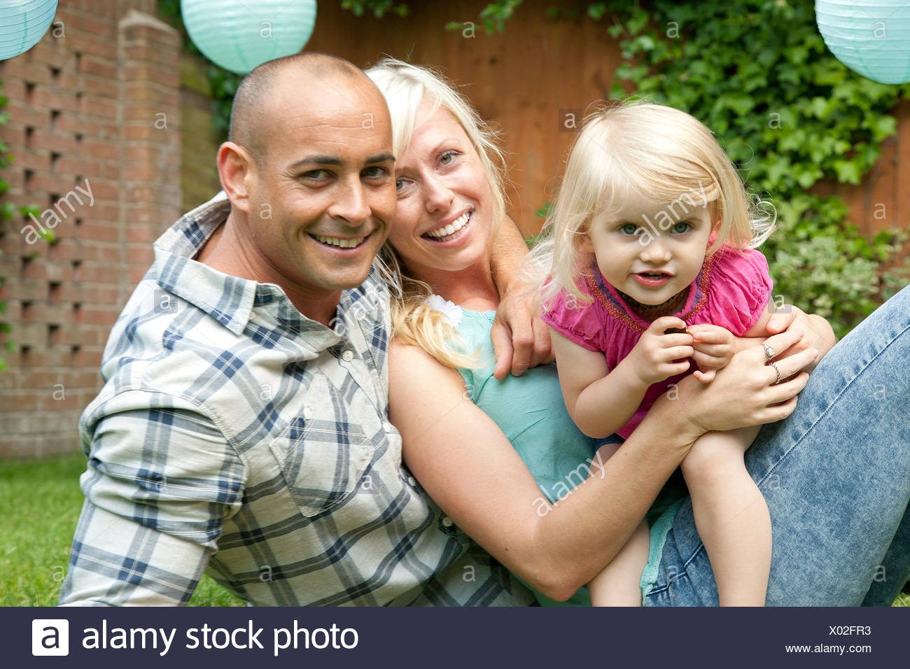 Portrait of happy couple sitting with toddler daughter in garden - Stock Image