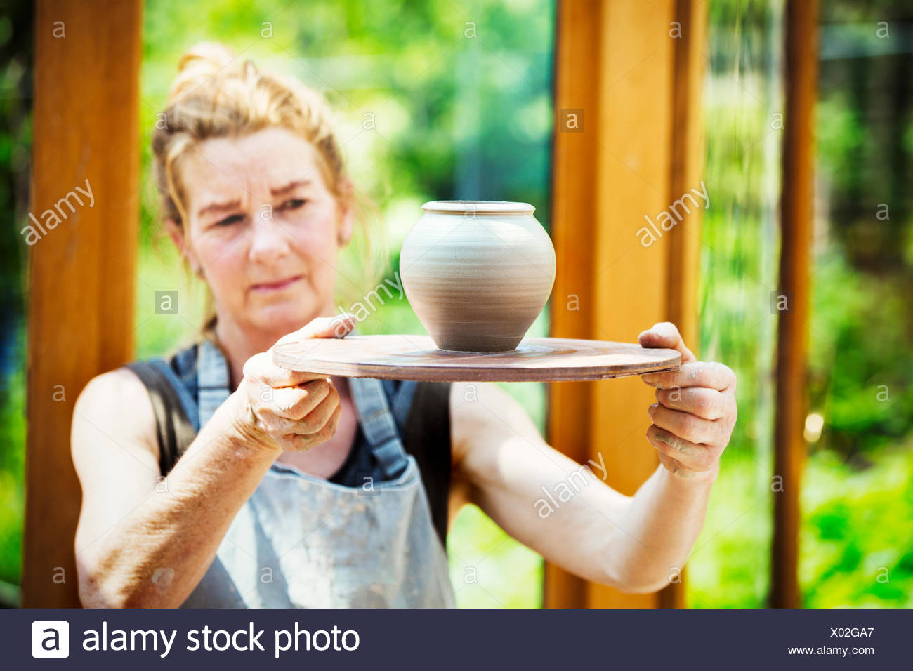A potter examining a hand thrown pot, wet clay slip, rounded vase with tapering sides. - Stock Image