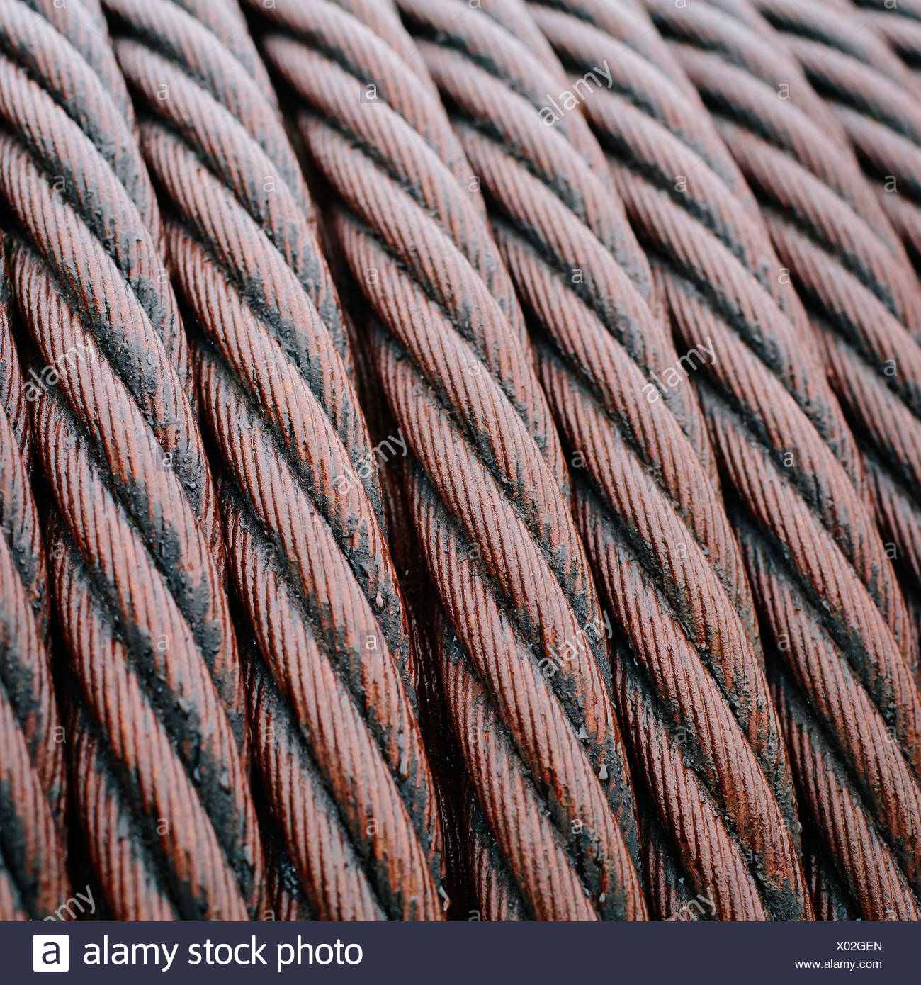 Close up of industrial steel hawsers stored neatly. - Stock Image