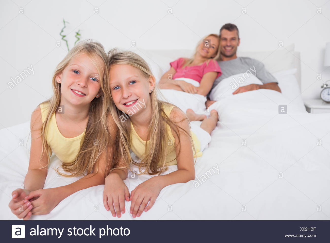 Twins posing in bed in front of their parents Stock Photo