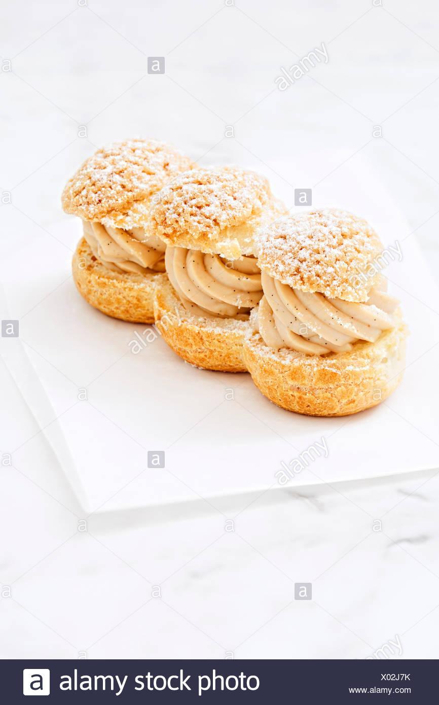 Cream puffs filled caramel cream custard on marble counter - Stock Image