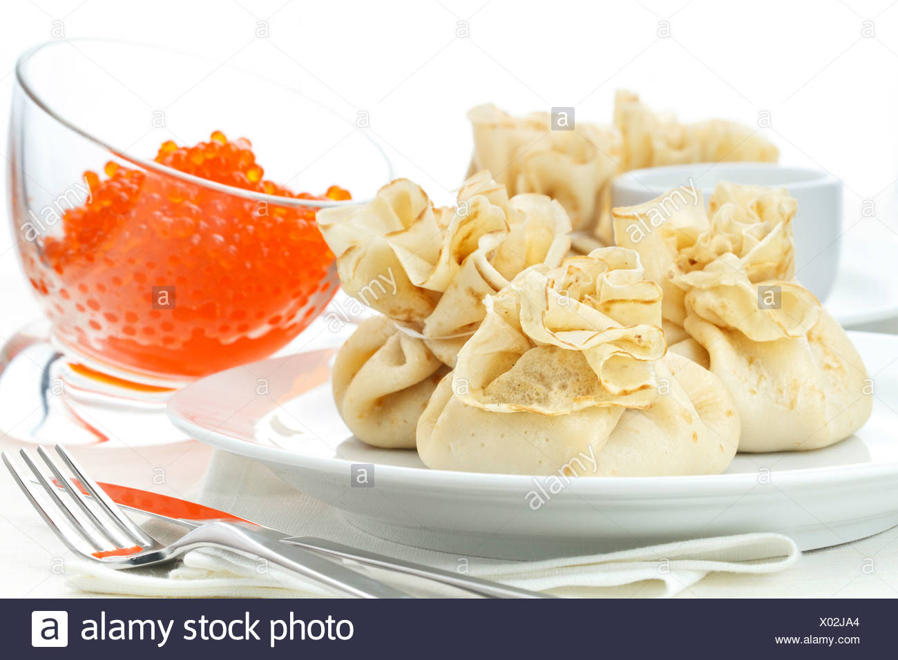 Pancake pouches with red caviar on white background - Stock Image
