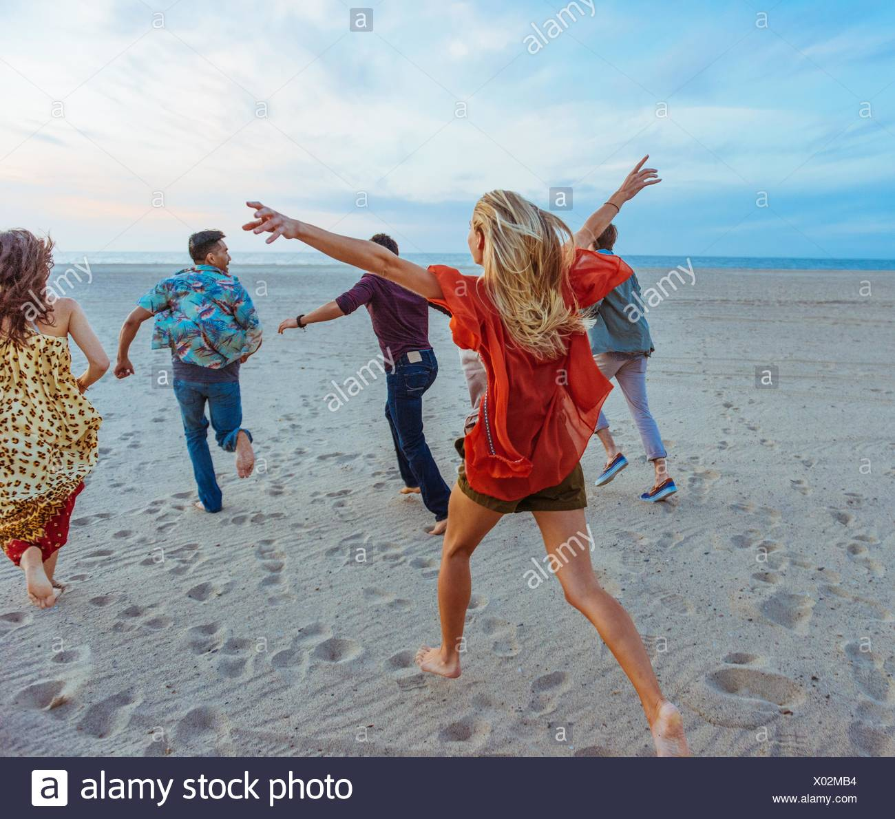 Group of friends walking along beach, young woman with arms in air, rear view - Stock Image