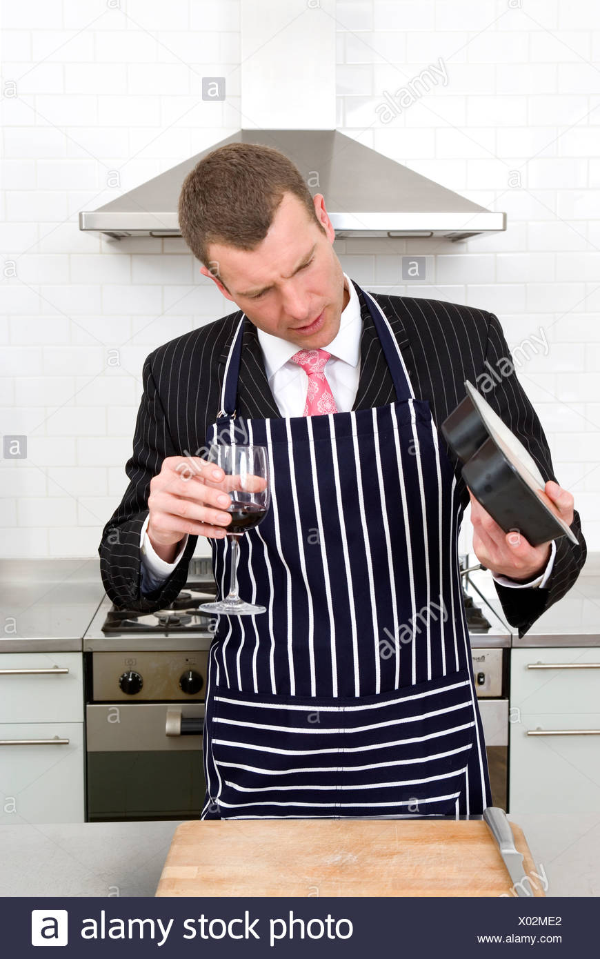 Businessman preparing a meal in the kitchen - Stock Image