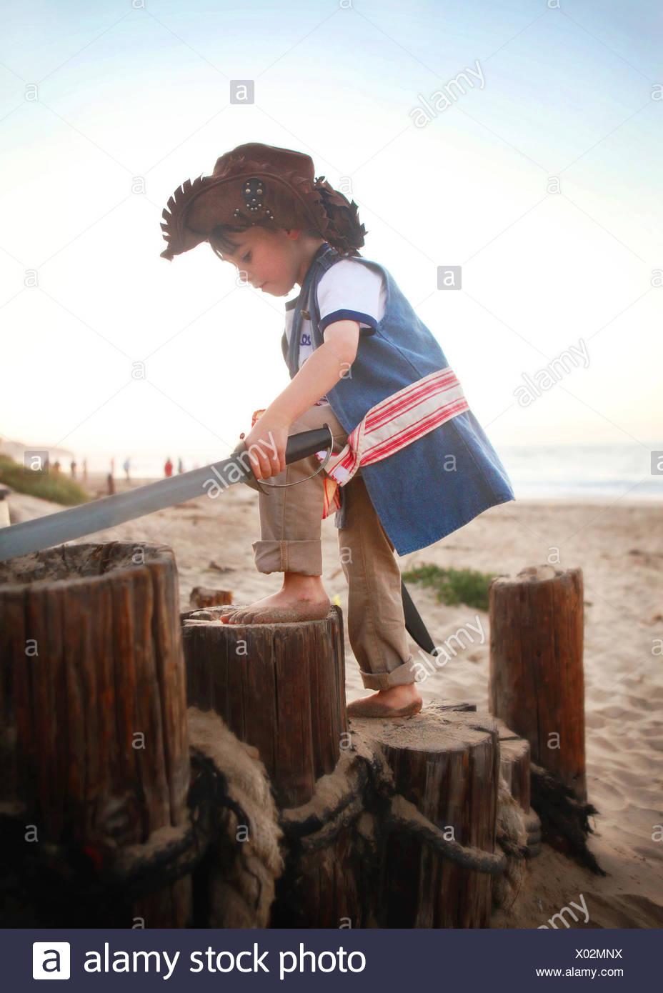 Boy in pirate costume on beach Stock Photo