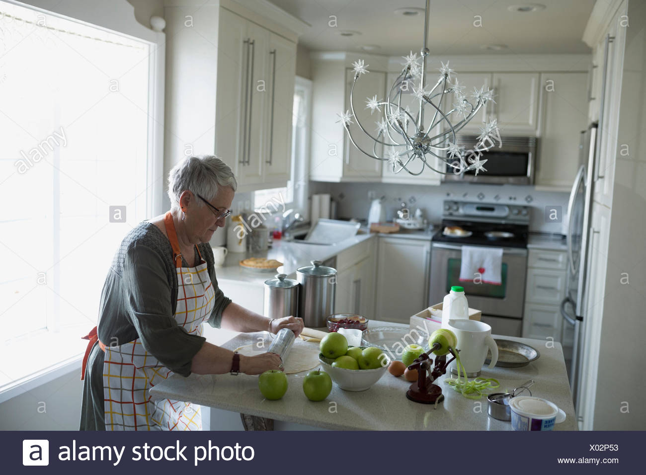 Senior woman rolling pie crust dough with rolling pin in kitchen - Stock Image