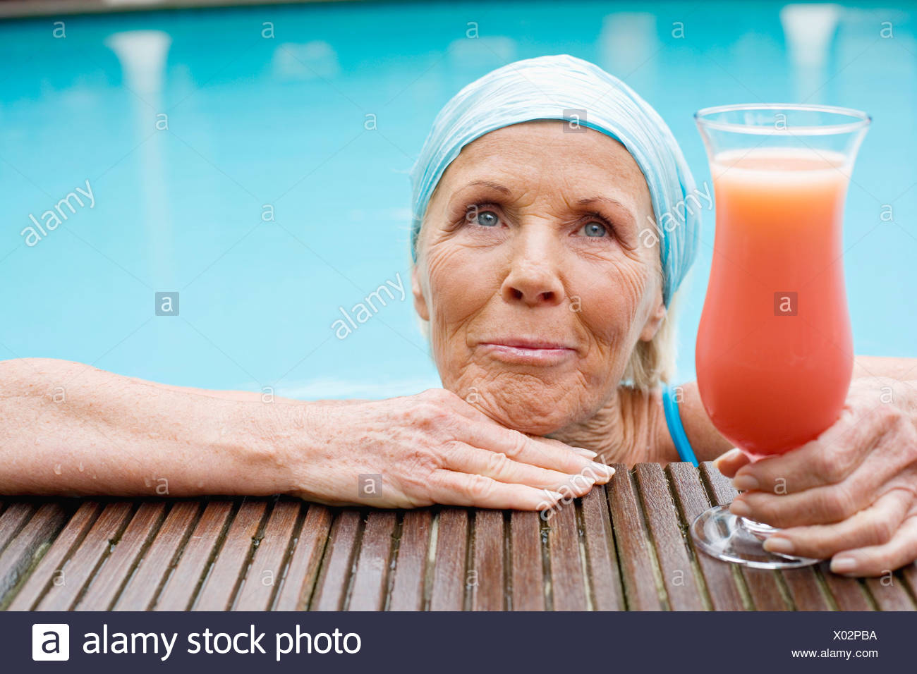 Germany, senior woman having cocktail at pool - Stock Image