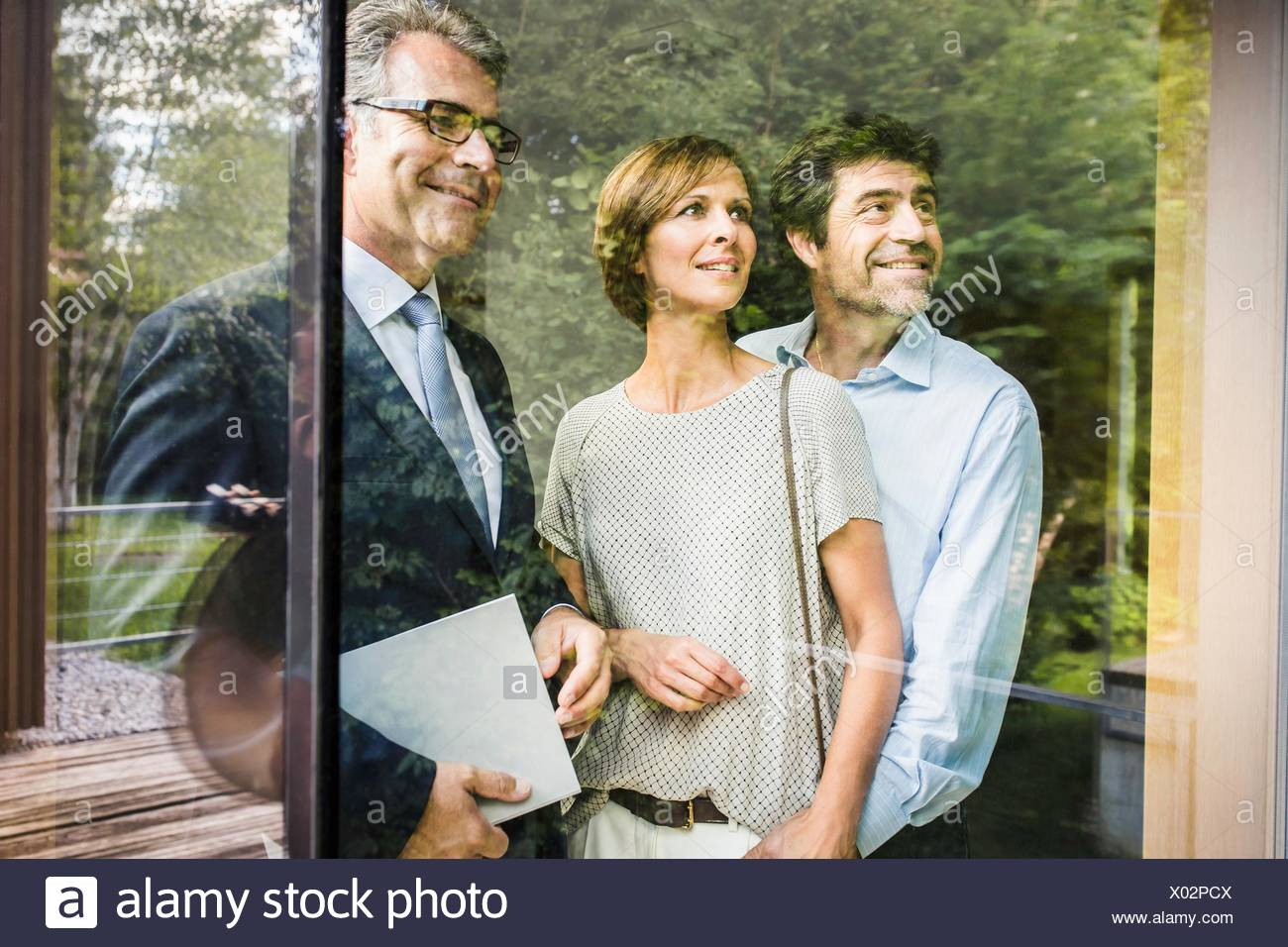 Estate agent with mature couple looking through window of  new house - Stock Image