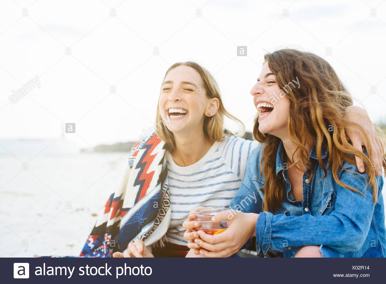 Two young female friends laughing on beach - Stock Image