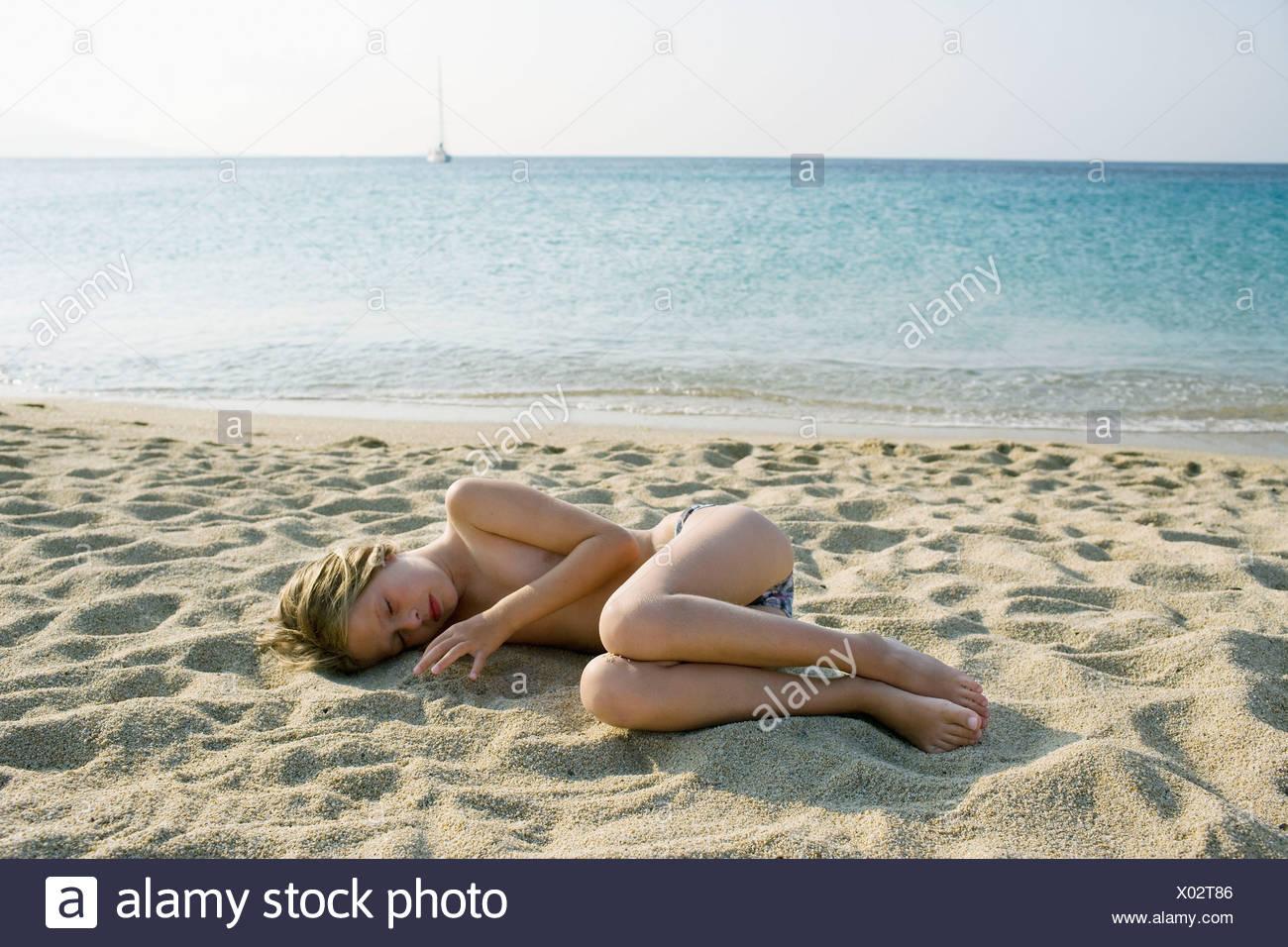 Young girl lying on the beach sleeping. Stock Photo