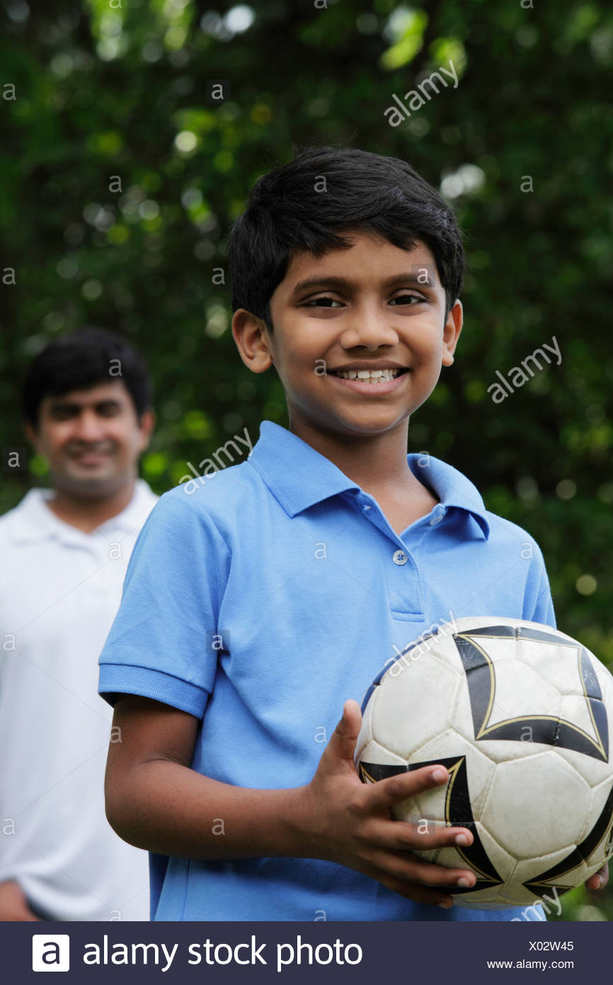 Young boy holding ball while father stands behind him - Stock Image