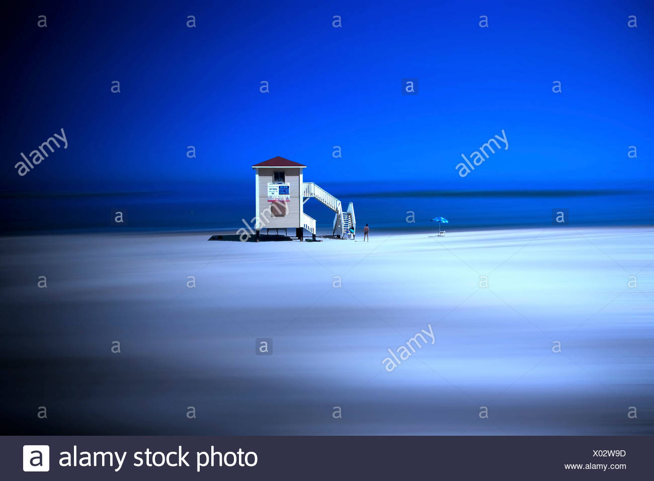 Scenic view with distorted landscape and sky with watch tower with silhouetted figures - Stock Image