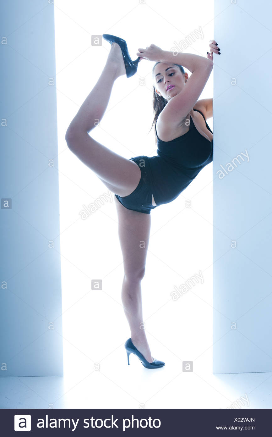 Athletic Busty Woman Posing In Doorway, ballet pose on one leg, wearing high heels and a leotard - Stock Image