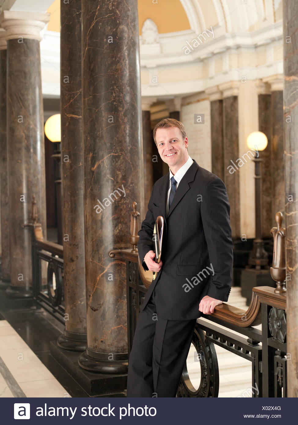 Confident lawyer leaning against railing in corridor - Stock Image