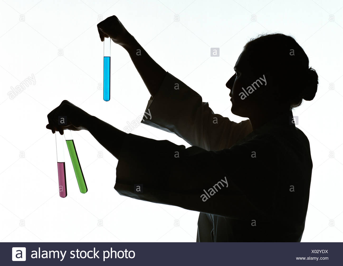 Woman holding test tubes containing different colored liquids, silhouette. - Stock Image