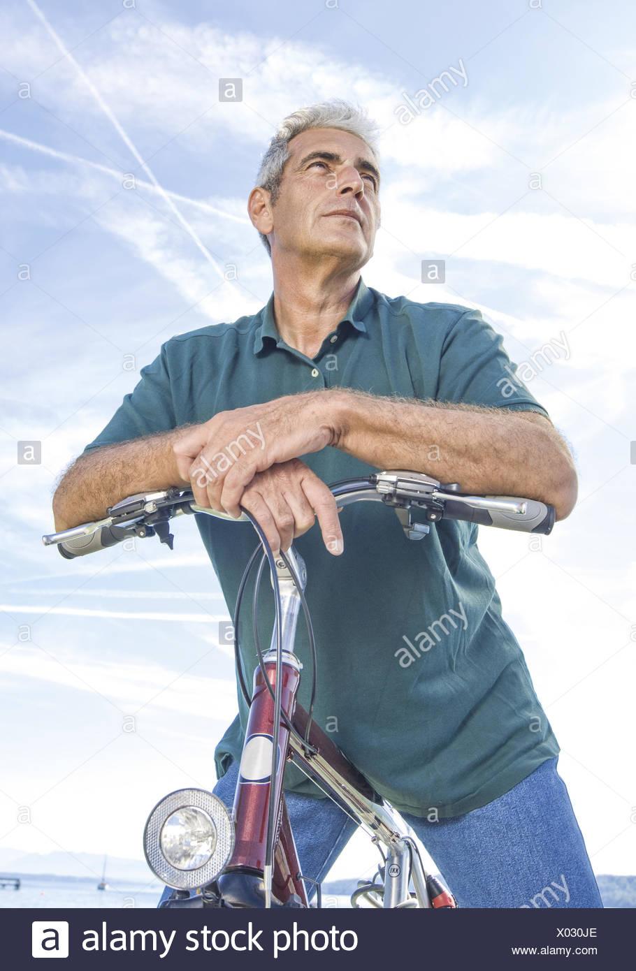 Senior auf Fahrrad, gegen Himmel (model-released) - Stock Image