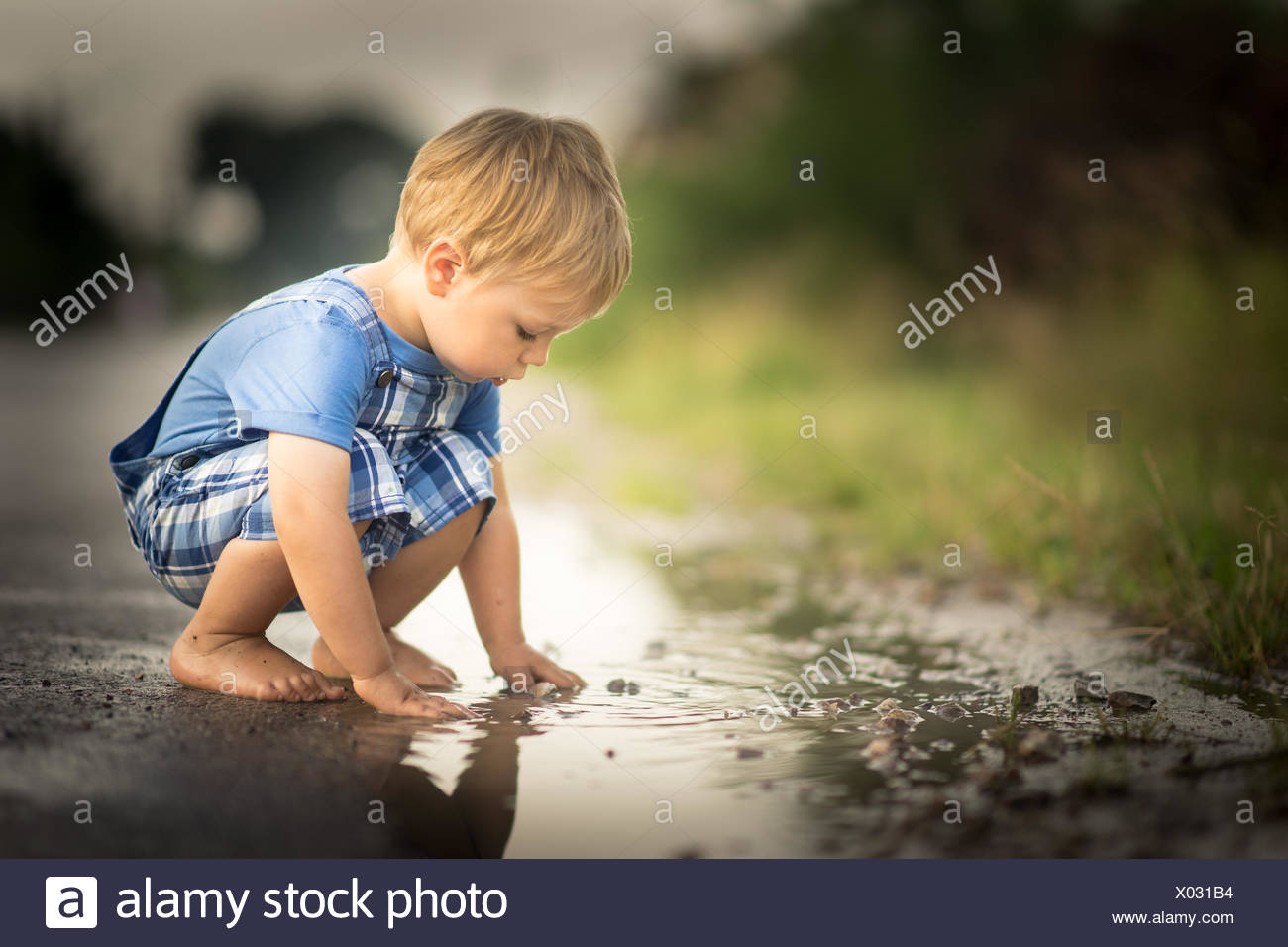 Boy playing in a puddle of water - Stock Image