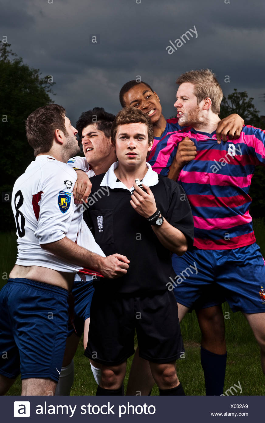 Referee with angry football players - Stock Image