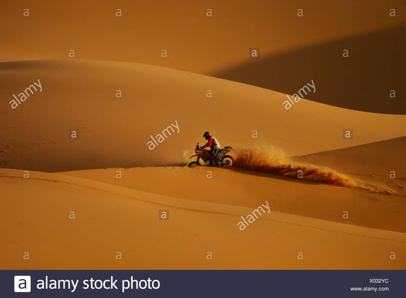 Offroad motorcycle motorbike motorcyclist adventure erg Chebbi desert sand dunes sand desert Merzouga Morocco North Africa - Stock Image