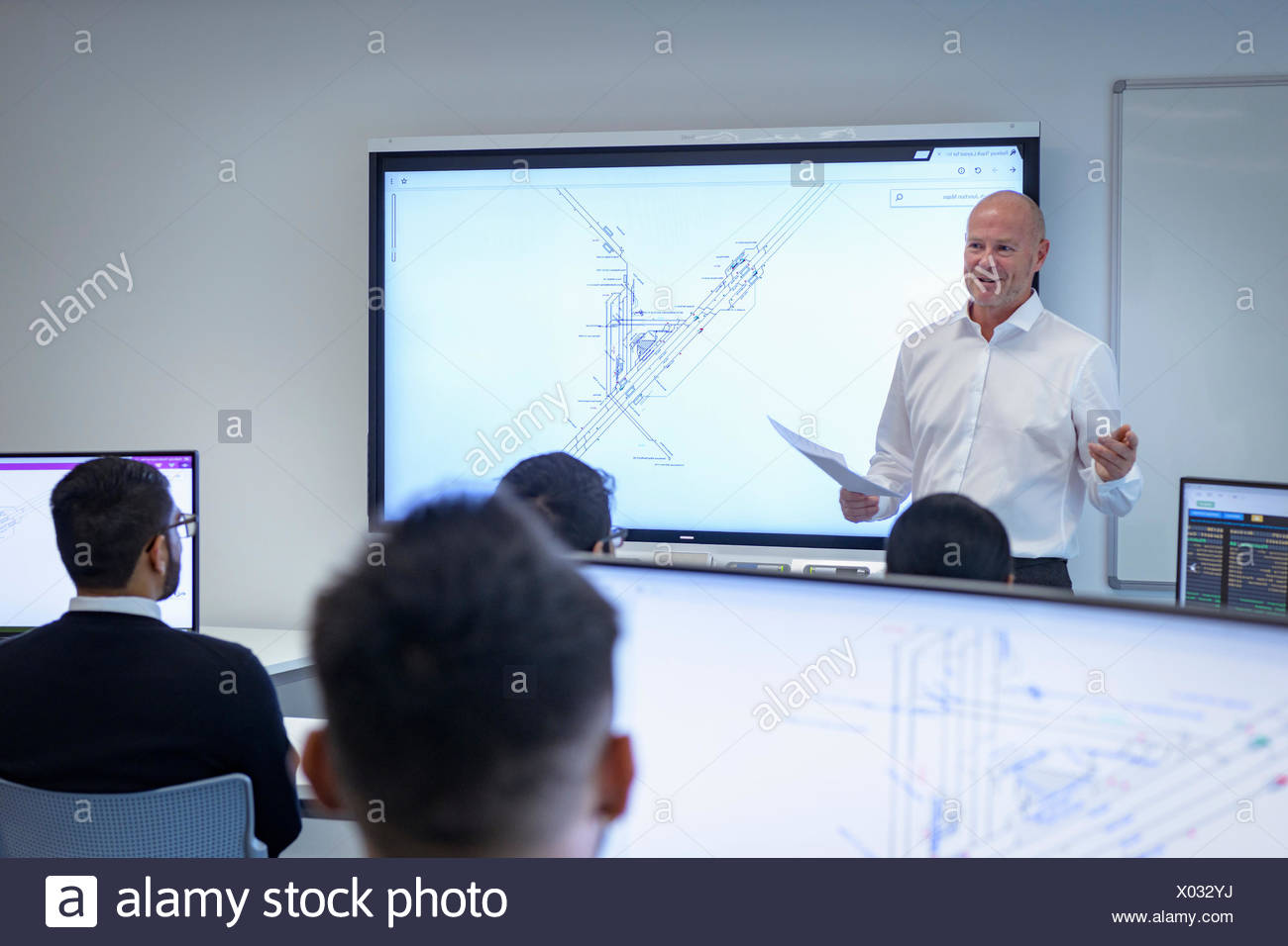 Teacher with apprentices studying screens in railway engineering facility - Stock Image