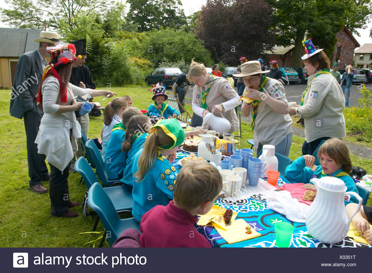 Scouts and cubs enjoying a mad hatters tea party at a countryside event - Stock Image