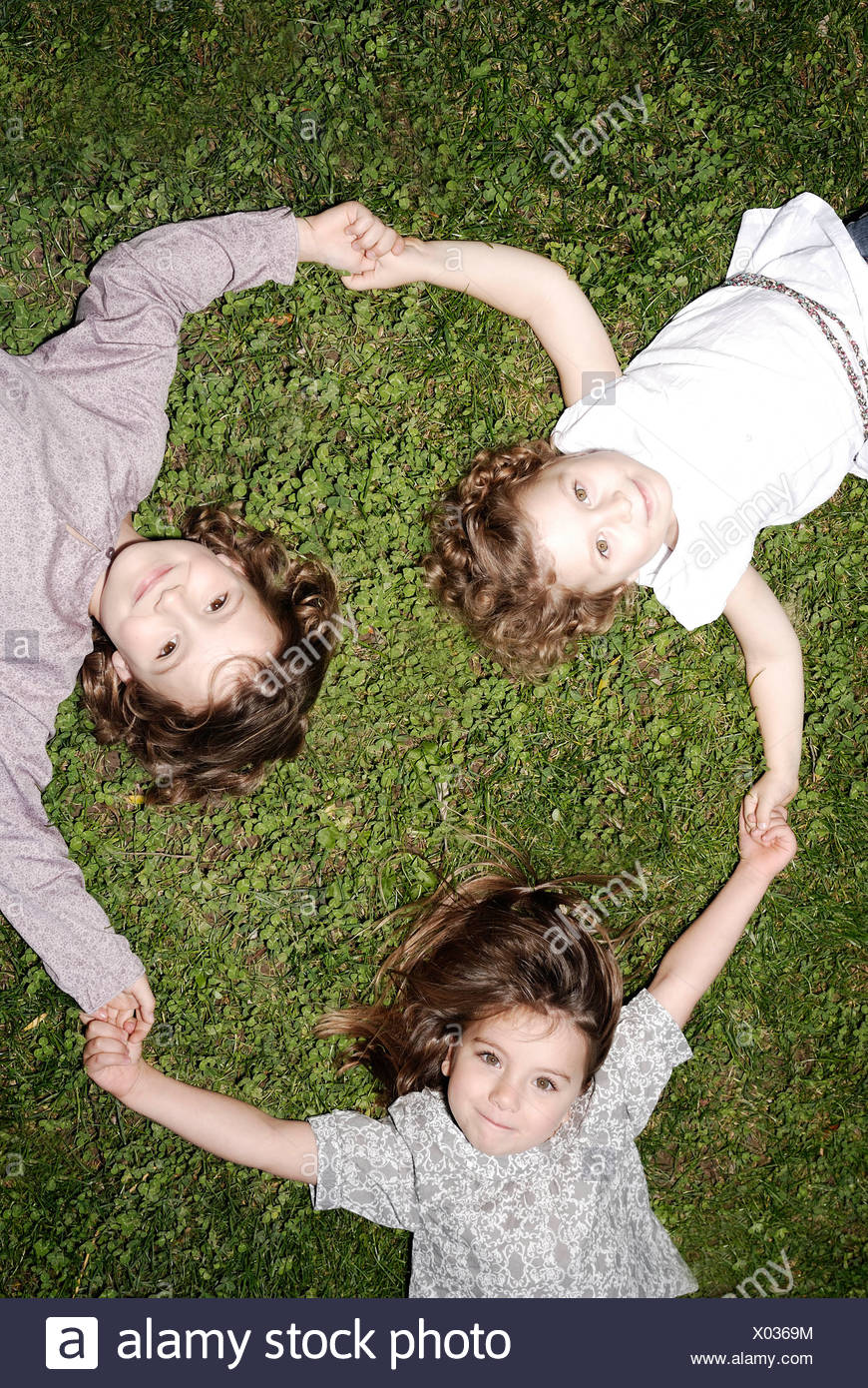 3 young girls holding hands - Stock Image