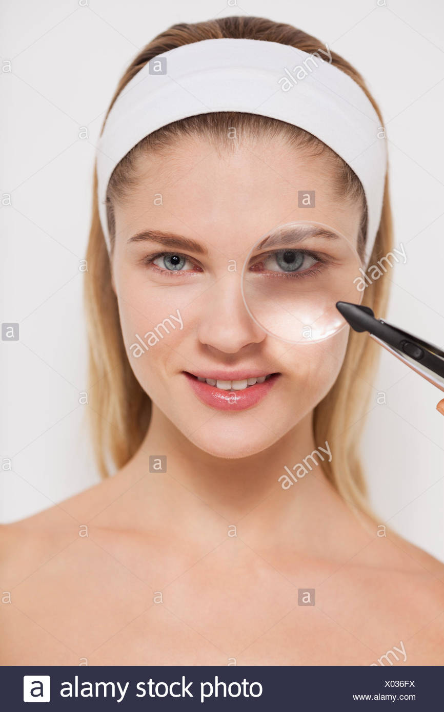 Beautiful woman looking through a magnifying glass - Stock Image