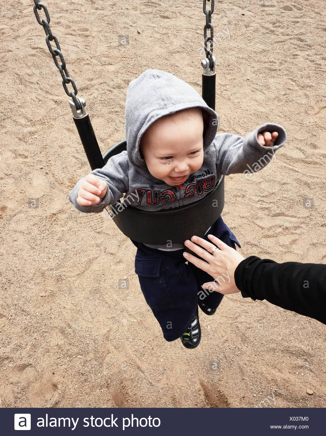 Cropped Image Of Parent Pushing Baby Boy In Swing At Park - Stock Image