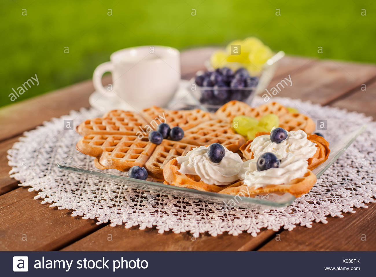 Sweet breakfast on wooden table in the garden. Debica, Poland - Stock Image