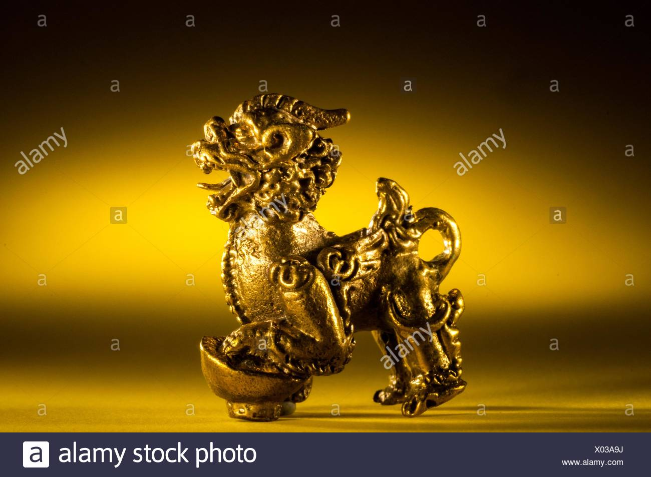 Brass amulet of 'pi-yao' lion for pursuit of wealth, from Thailand in studio setting. - Stock Image