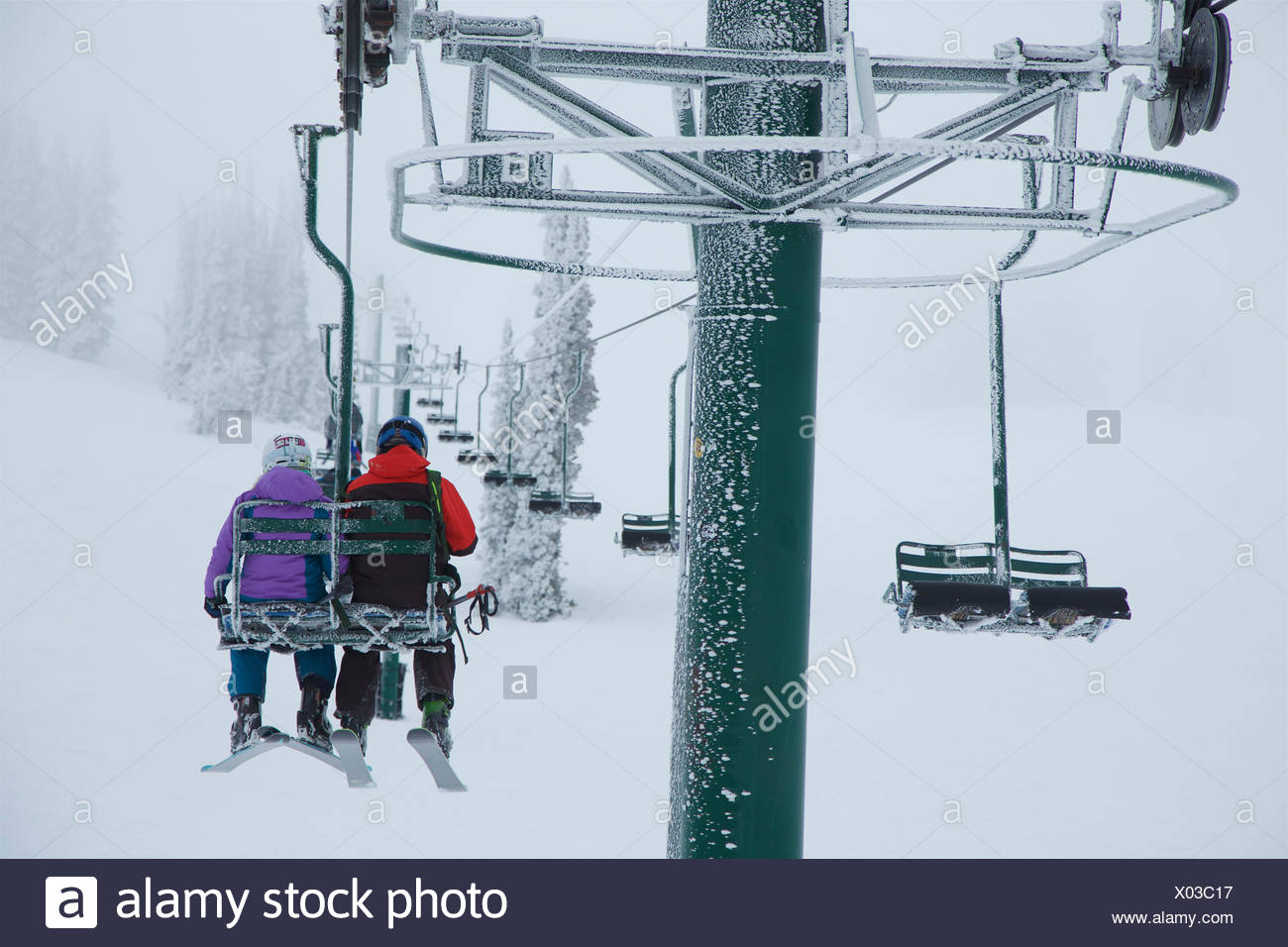 Siblings riding the chairlift to go skiing in stormy conditions. - Stock Image