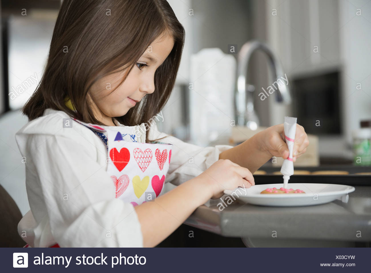 Girl decorating fresh baked cookie - Stock Image