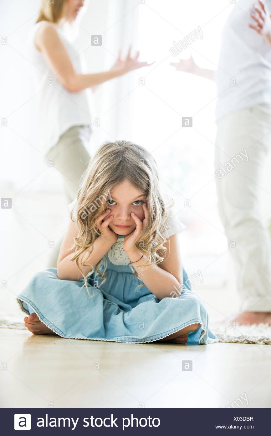 Little girl sitting cross-legged on floor, parents arguing in background - Stock Image