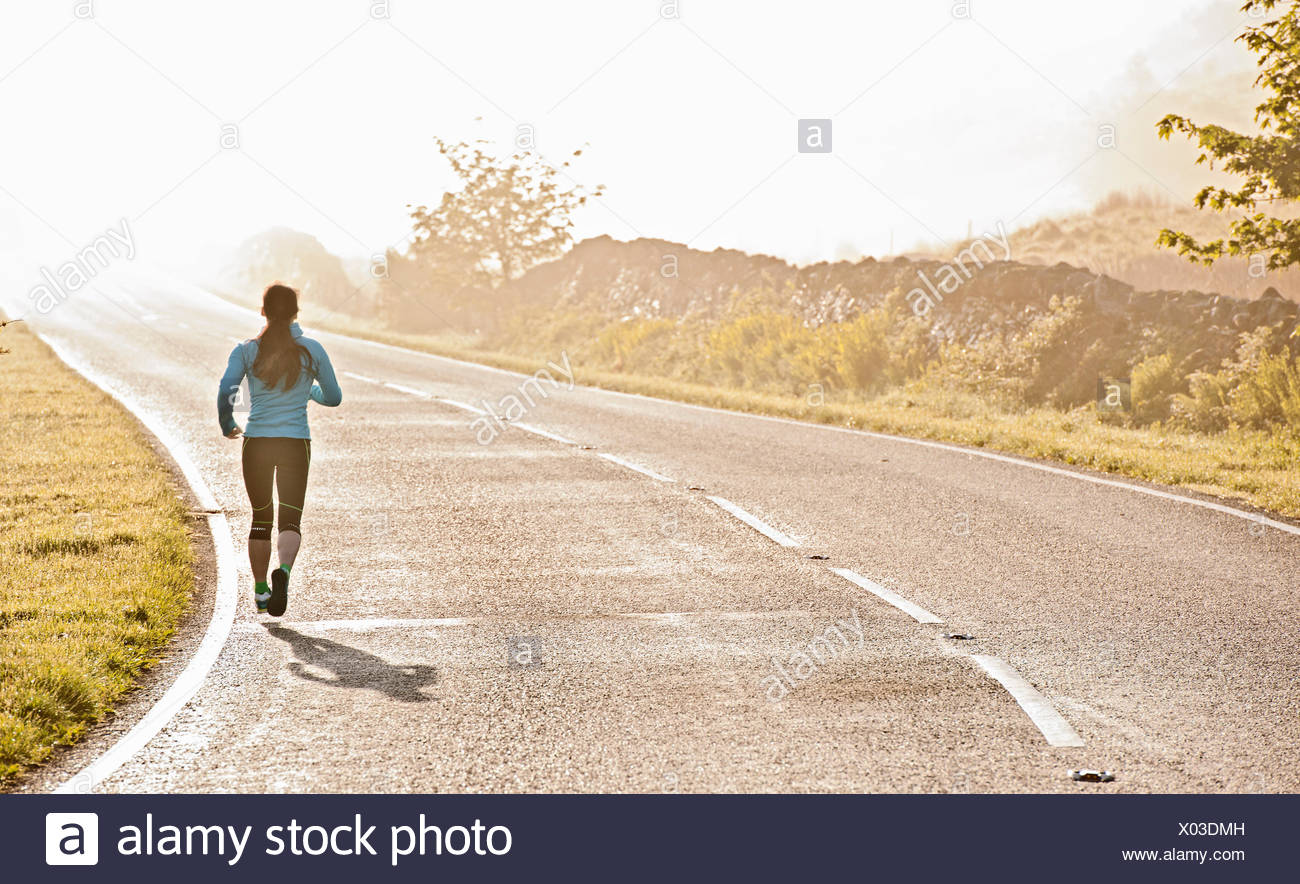 Rear view of female runner running on misty road, Capel Curig, Snowdonia, North Wales, UK - Stock Image