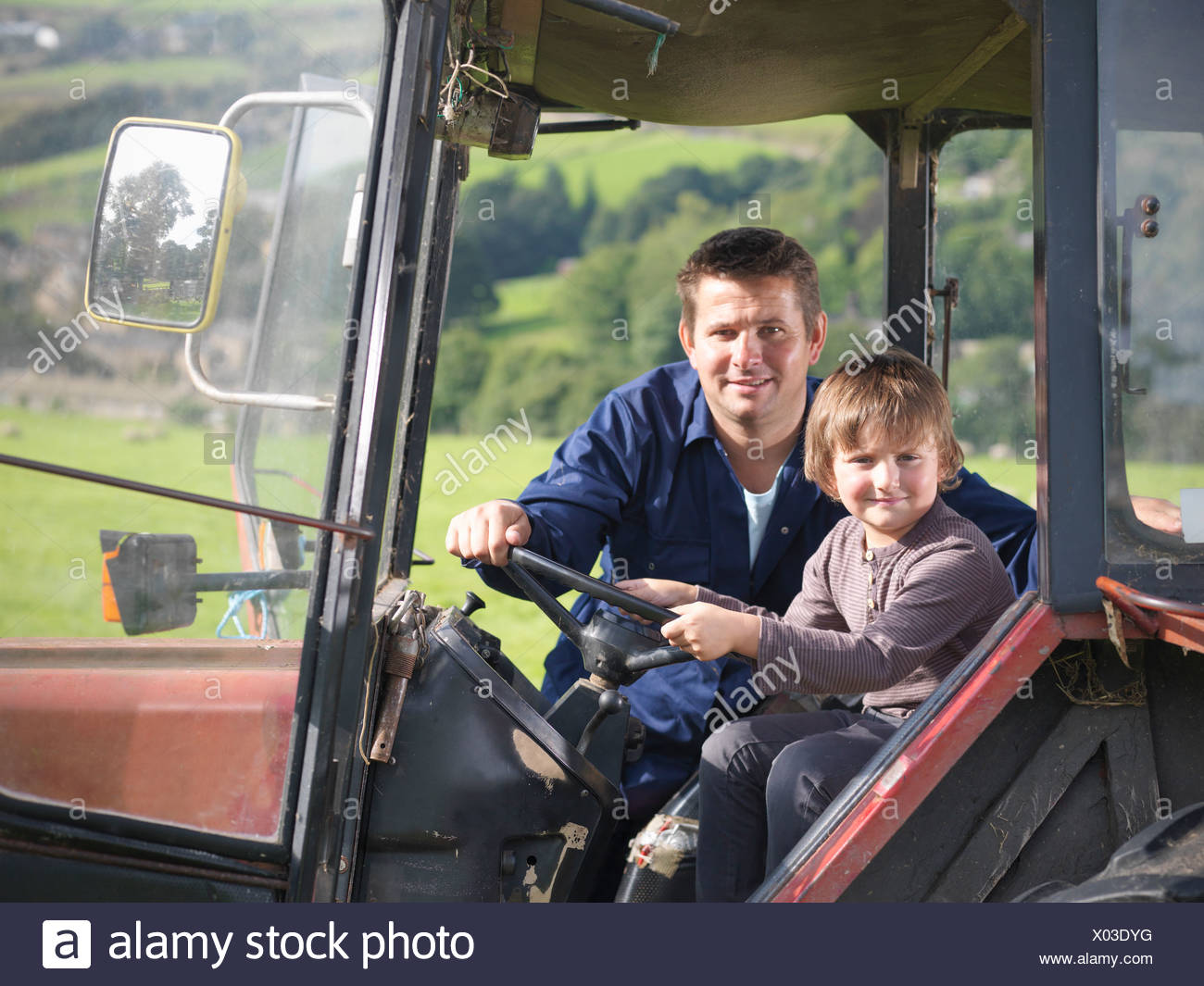 Farmer and young son in tractor in field, portrait - Stock Image