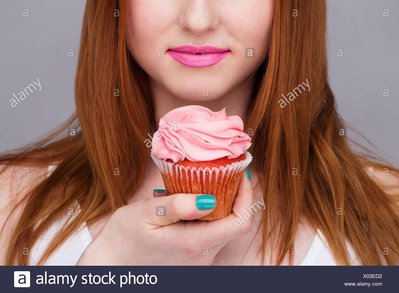 Cropped image of young woman holding cupcake - Stock Photo