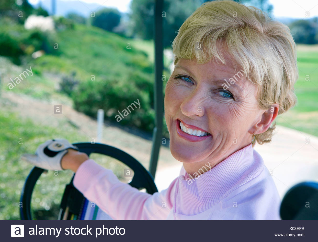 Mature woman driving golf buggy on golf course, looking over shoulder, smiling, close-up, rear view, portrait - Stock Image