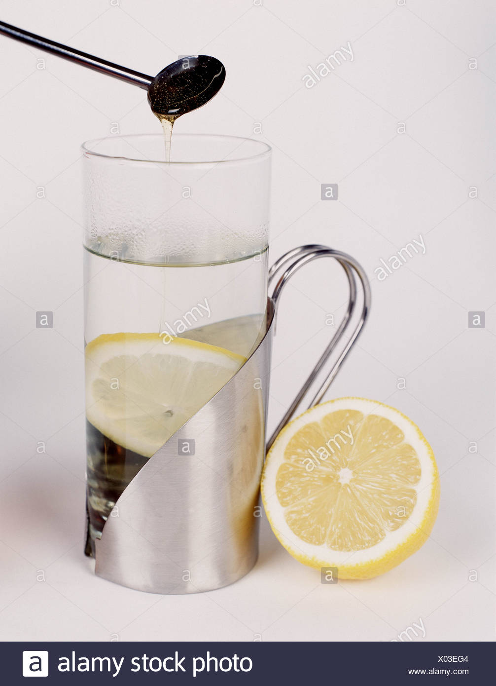 Silver mug with steamed glass containing hot water and a lemon slice silver spoon containing honey held over glass Stock Photo
