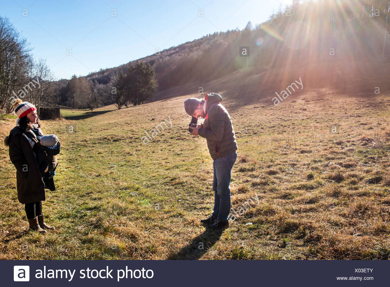 Man taking photograph of woman and baby boy, using medium format camera, in rural setting, Italy - Stock Image