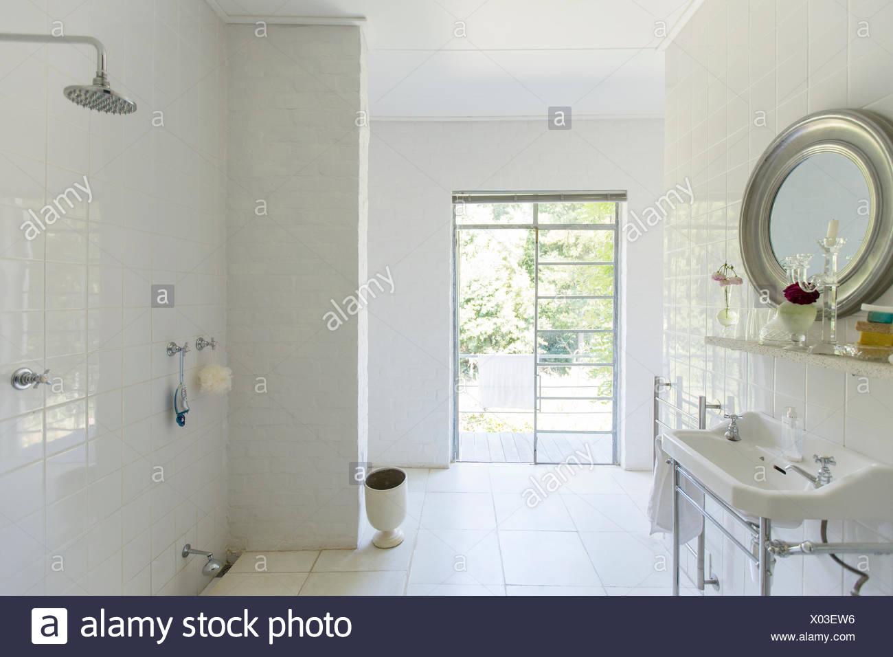 Glass door in rustic bathroom - Stock Image