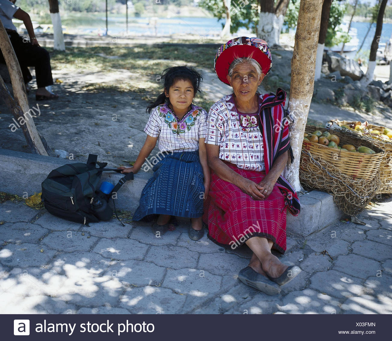 Guatemala, Atitlansee, Santiago, Atitlan, senior, girl, folklore clothes, no model release Latin America, highland region, Lago de Atitlan, locals, woman, child, granddaughter, folklore, clothes, tradition, culture, market, sales, fruits, economy, trade - Stock Image