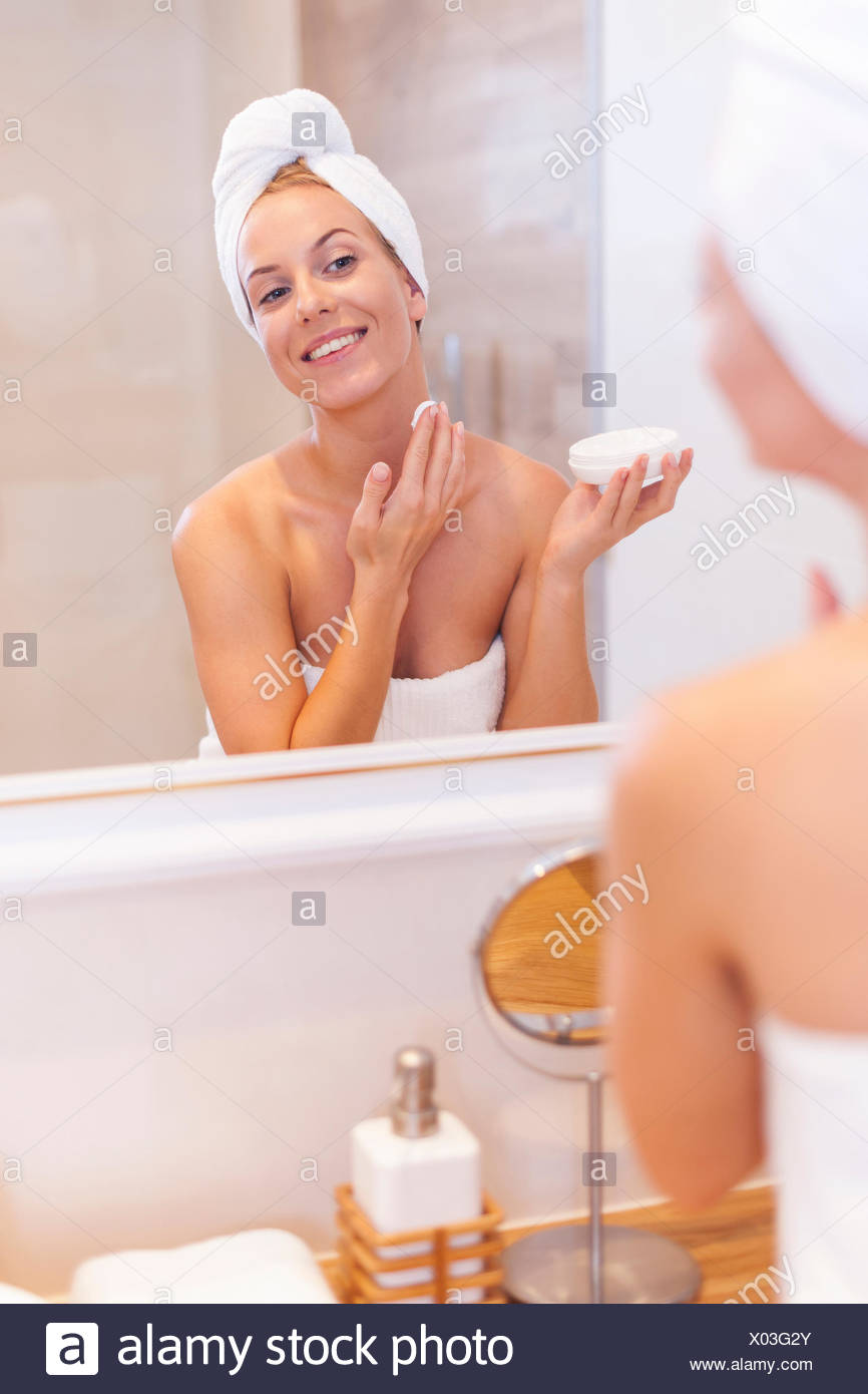 Young woman applying moisturizer on face after the shower. Debica, Poland - Stock Image