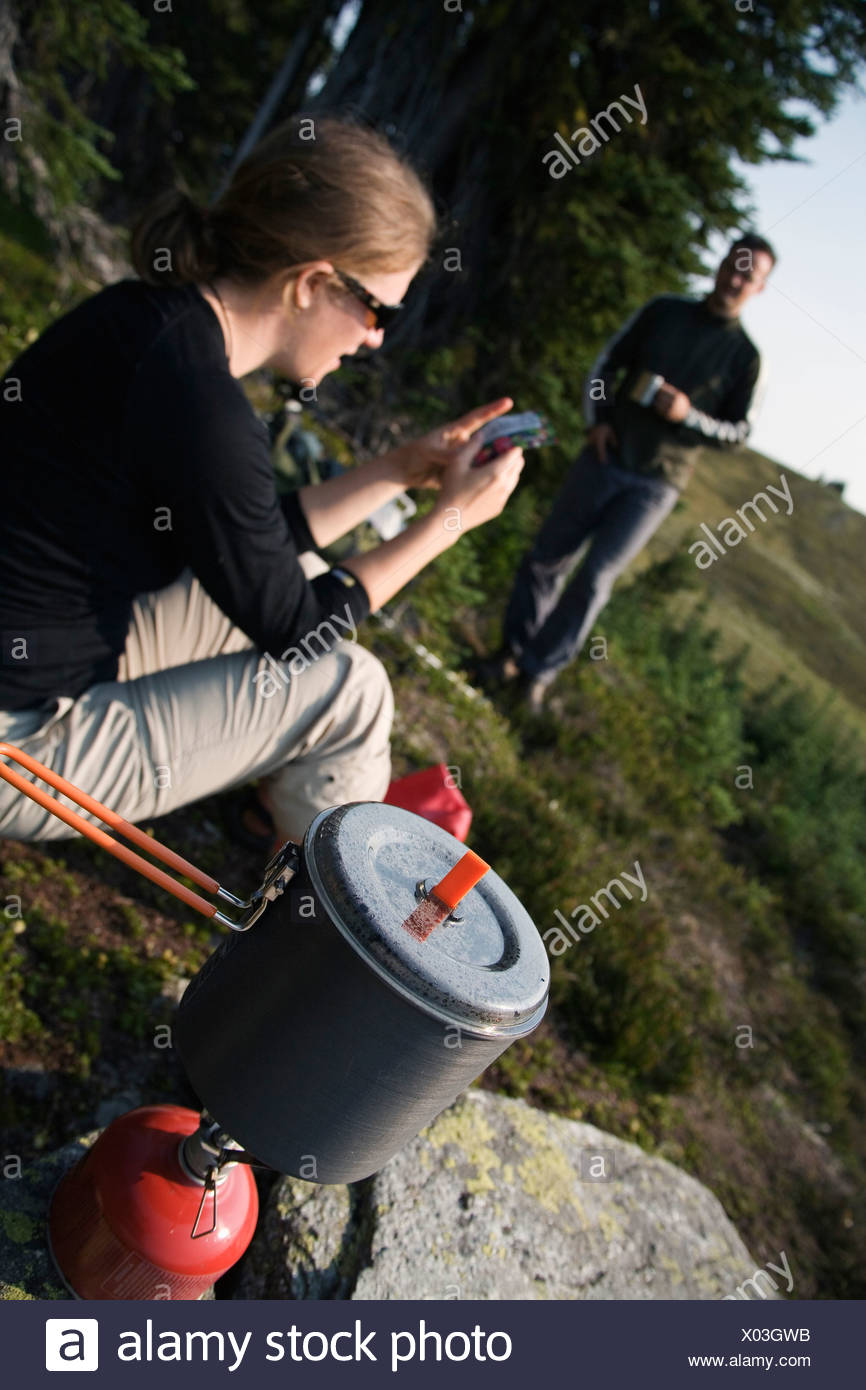 Two hikers wait while water boils on a canister-style camp stove in the Purcell Mountains. - Stock Image