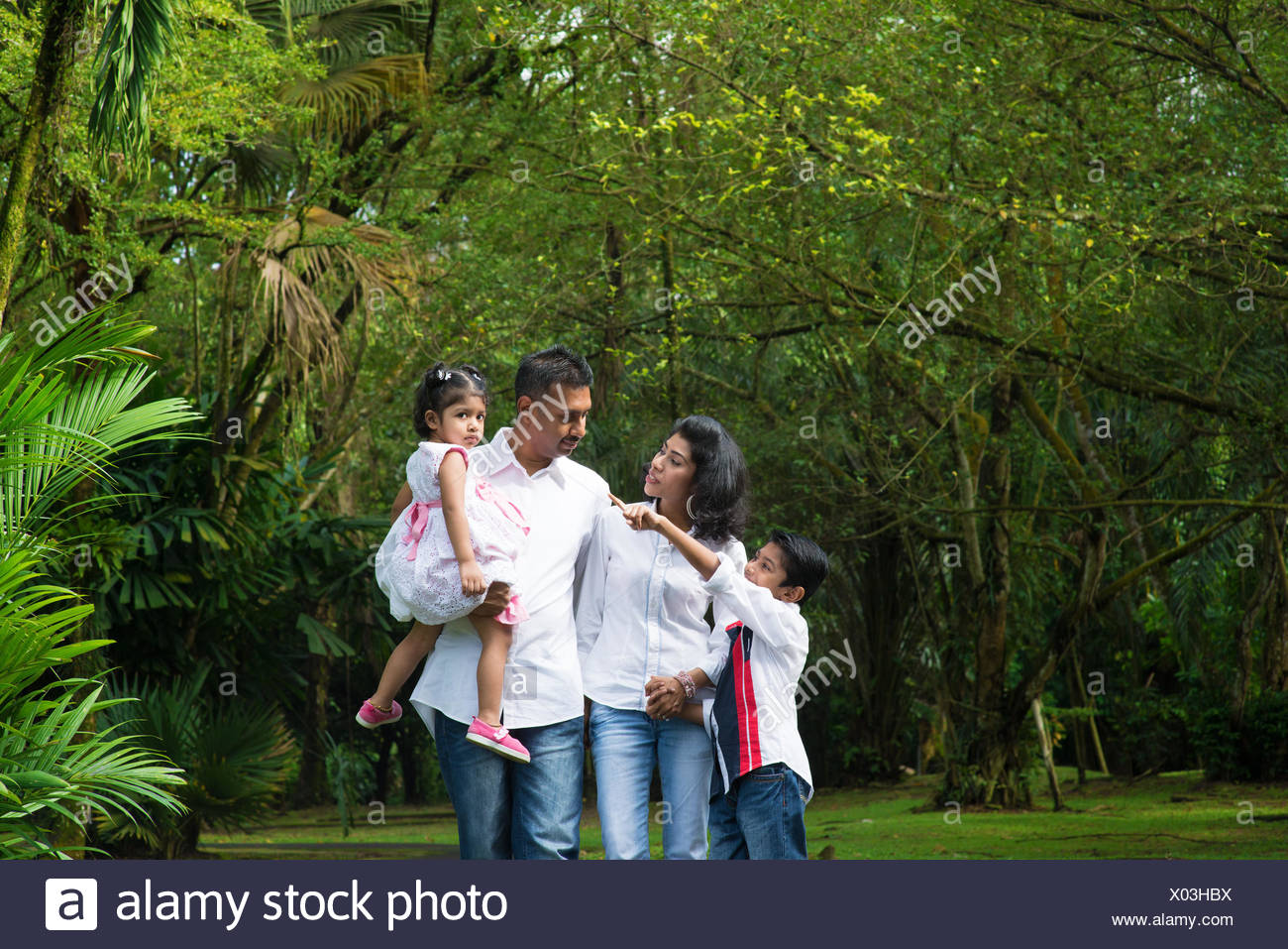 Indian family at outdoor. Parents and children walking on garden path. Exploring nature, leisure lifestyle. - Stock Image