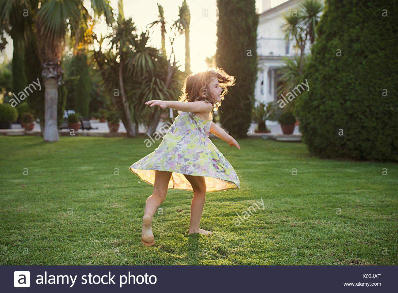 Girl spinning around in garden - Stock Image