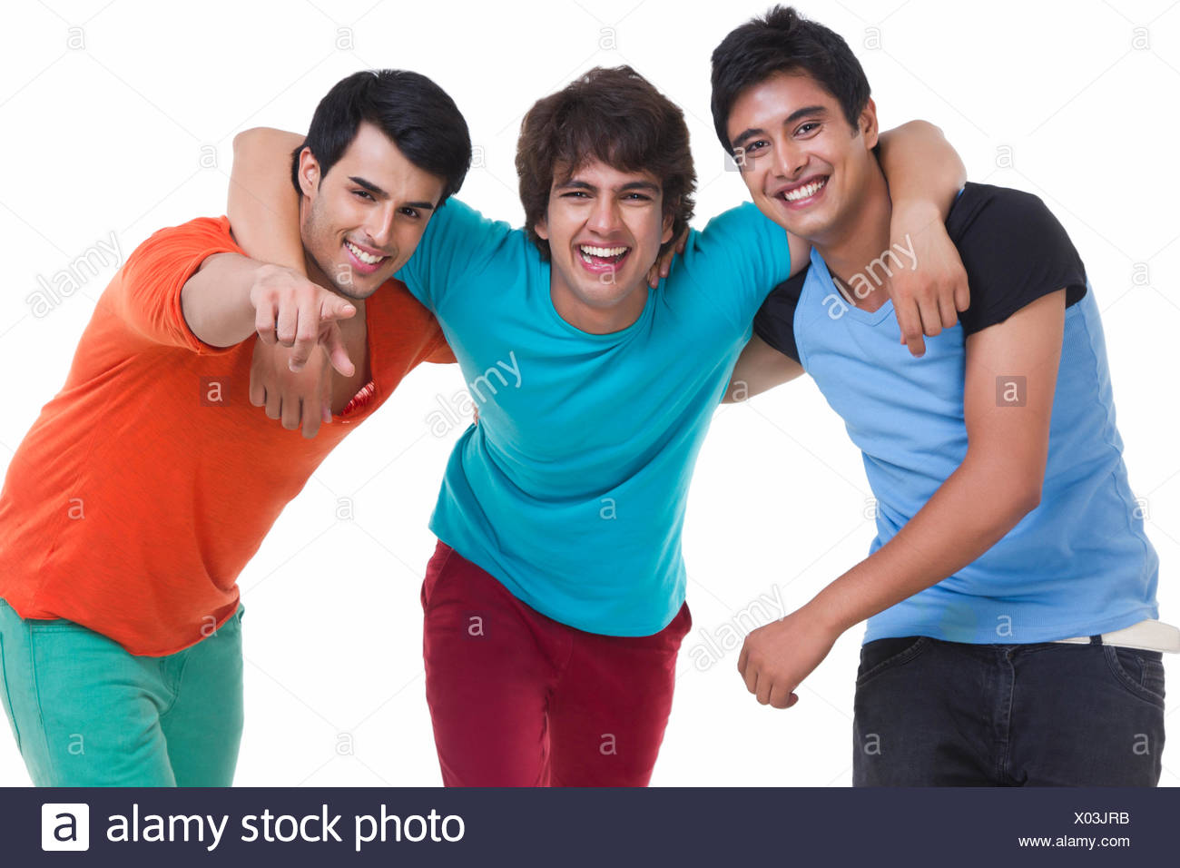 Playful young male friends with arm around over white background - Stock Image