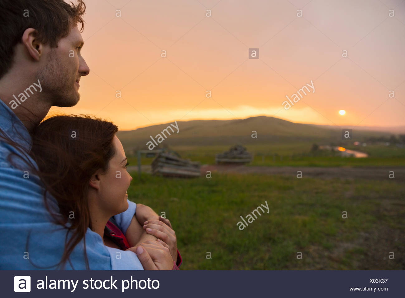Serene couple watching sunset over rural field - Stock Image