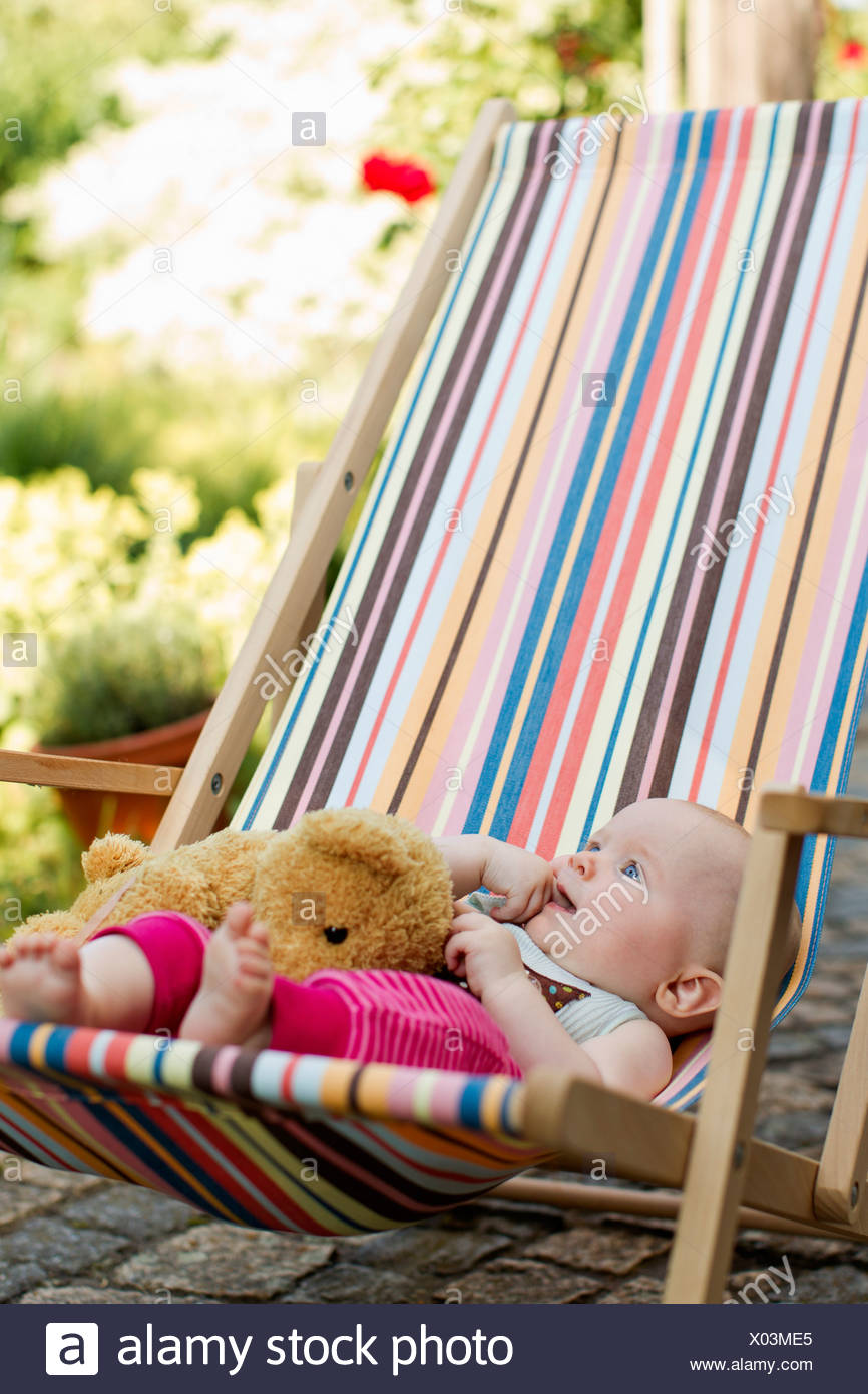 Baby girl sitting on deck chair with teddy bear - Stock Image