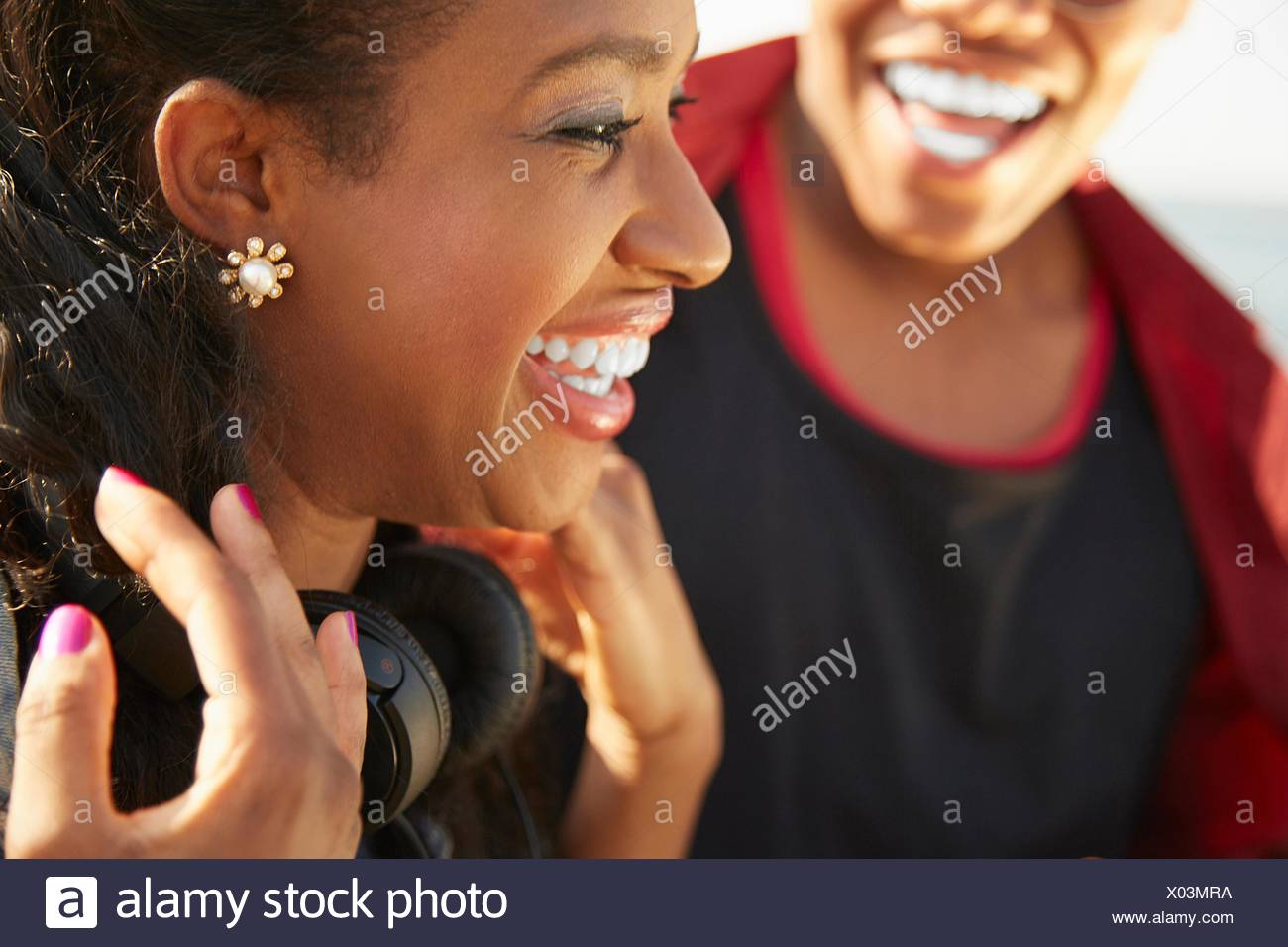 Close up profile of young woman smiling wearing headphones, people in background - Stock Image