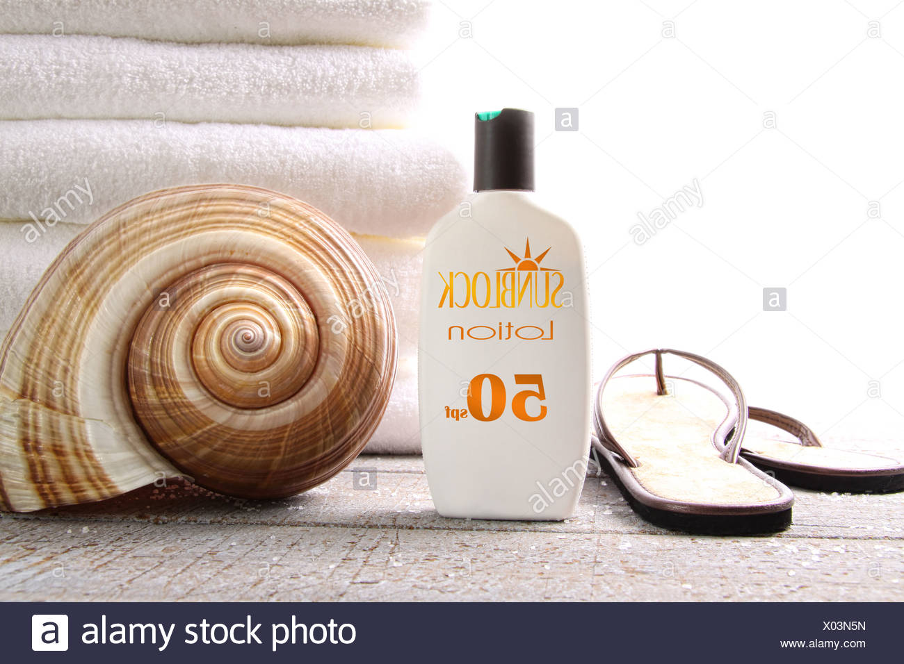 Sunblock lotion, sandals and white towels on white - Stock Image